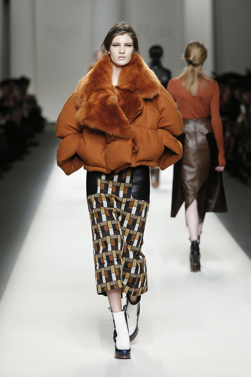 Rust orange wool gauze jacket with shearling collar and long printed wool skirt with leather pockets.By Fendi